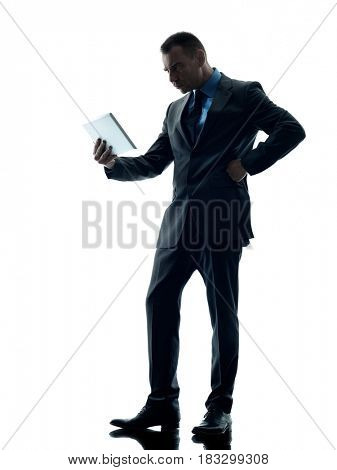 one caucasian business man standing using digital tablet  angry silhouette isolated on white background