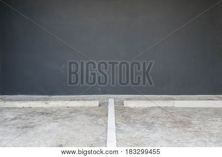 Closeup surface line slot for parking on cement floor with blurred dark gray cement wall in the garage textured background with copy space
