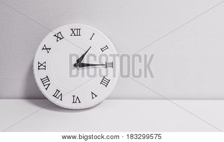 Closeup white clock for decorate show a quarter past one o'clock or 1:15 p.m. on white wood desk and wallpaper textured background in black and white tone with copy space