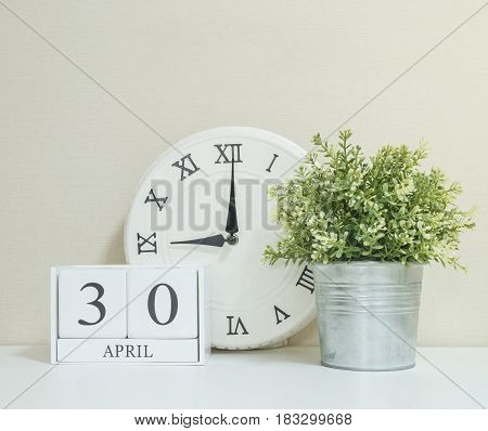 White wooden calendar with black 30 april word with clock and plant on white wood desk and cream wallpaper textured background selective focus at the calendar