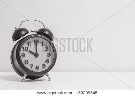 Closeup alarm clock for decorate in 10 o'clock on white wood desk and cream wallpaper textured background in black and white tone with copy space