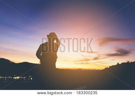 Silhouette of man hipster looking sunshine  and mountain view.