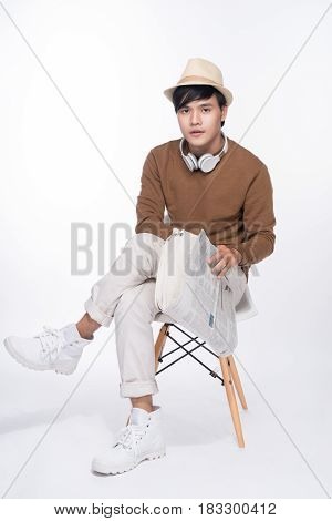 Smart Casual Asian Man Seated On Chair, Reading Newspaper In Studio Background