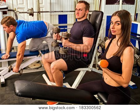 Woman holding dumbbell workout at gym. Girl with bare belly. Friends men with heavy dumbbells on background. Barbell in background. Body that you want concept.
