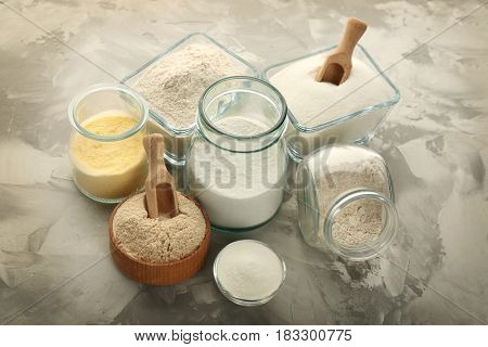Composition with different types of flour on grey textured background