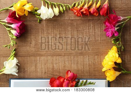 Frame made of beautiful freesia flowers on wooden background