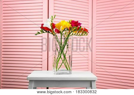 Vase with beautiful bouquet of freesia flowers indoors