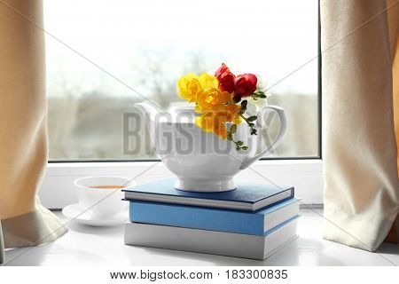 Composition with beautiful freesia flowers on window sill