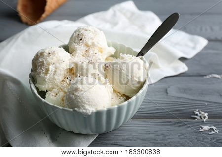 Bowl with balls of ice cream and desiccated coconut on grey wooden table
