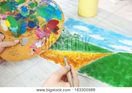 Hand of painter creating colorful landscape made with oil paint strokes, closeup