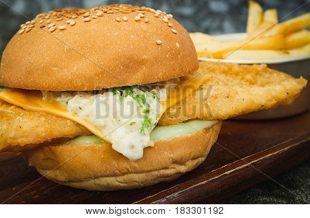 A fresh made Fish Burger on wooden plate (close-up shot; selective focus)