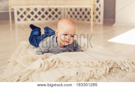 Adorable baby boy in sunny bedroom. Newborn child relaxing. Nursery for young children.Family morning at home. Little kid lying on tummy.
