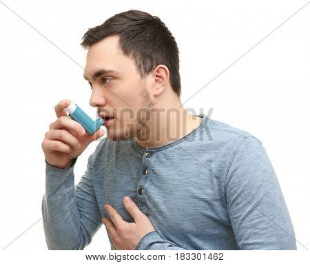 Young man using inhaler during asthmatic attack, on white background