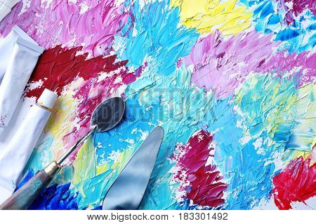 Used tubes of oil paints and palette knives on created picture, closeup