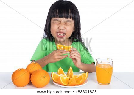 Asian Chinese little girl eating sour orange and making grimace in isolated white background poster