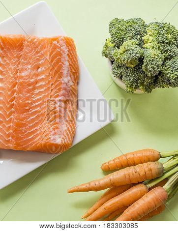 portions of fresh salmon fillet and vegetables