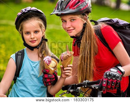 Mother and daughter on bicycle. Happy family eating ice cream and ride bike . Bikes cycling family. Kid practice to riding in summer park.