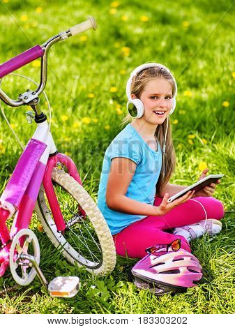 Bicycle child wearing headset listening music. Girl resting and playing on tablet pc. Kid sitting green grass watching at touch screen gadget.