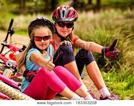 Mother and daughter on bicycle. Bikes cycling family. Happy mother and daughter are sitting on green grass road near bicycles. Cycle racing concept.