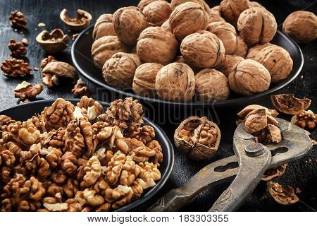 Walnuts. Nuts of walnuts. Tongs for cutting nuts. Pure organic walnuts. Nuts in black plates against the background of a black wooden background. Agriculture. Fresh autumn walnut harvest in the village