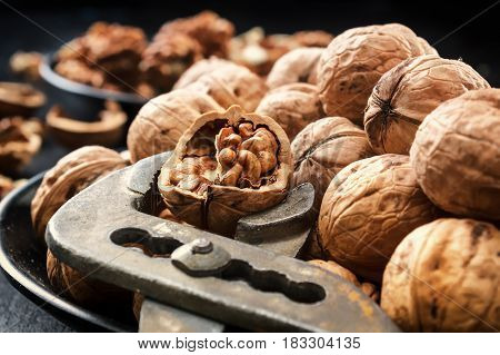 Walnuts. Nuts of walnuts. Nippers for cutting nuts. Scoop of walnuts. Nuts in black plates against the background of a black wooden background. Agriculture. Fresh autumn walnut harvest in the village