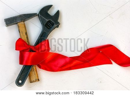 International Worker Solidarity Day 1 May concept hammer and wrench with red tape on a white textured surface