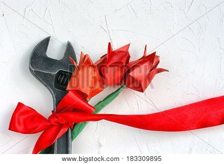 International Workers' Solidarity Day 1 May concept wrench with red ribbon and origami tulip on white textured surface