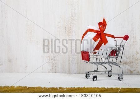 Shopping Cart With Gift Box On A Light Wooden Background