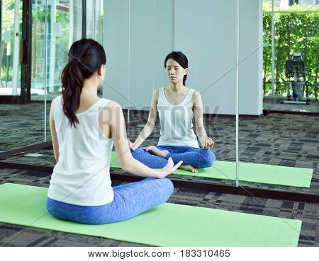 Young Woman Meditating In Front Of Mirror In Yoga Room, Yoga Concept