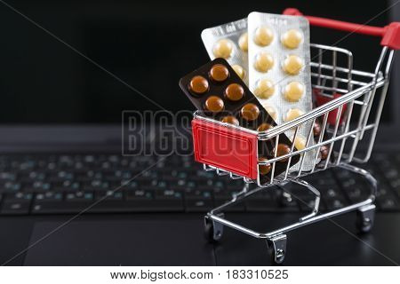 Shopping Cart With Pills On A Laptop.