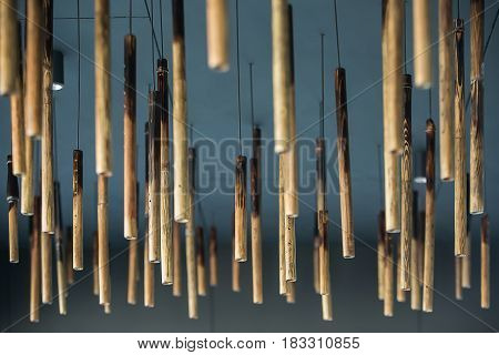 Closeup photo of many hanging wooden tubes. Low aperture photo. Horizontal.