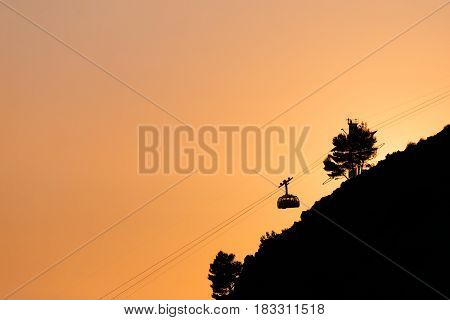 Cableway or ropeway to Mount Srdj in Dubrovnik, Croatia against the background of the orange sky.
