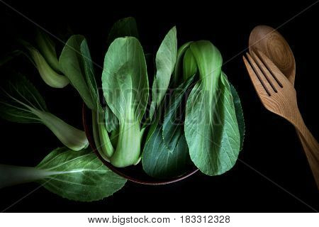 close up Fresh baby green bok choy in bowl with wodden spoon and fork on black background overhead or top view shot