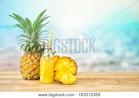 Bottles of pineapple juice with sliced pineapple fruit on wooden table with abstract blue sea background summer fruit drink concept