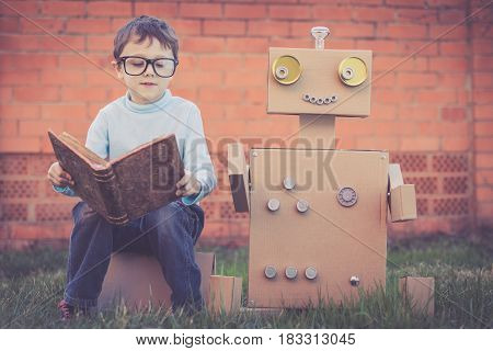 One Little Boy Reading To  Robot From Cardboard Boxes Outdoors.