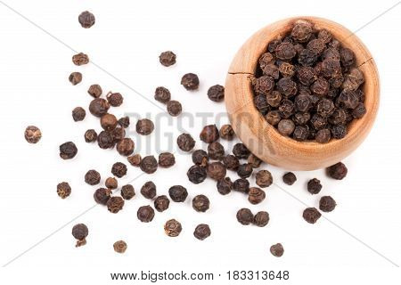 Black peppercorn in a wooden bowl isolated on white background. Top view.