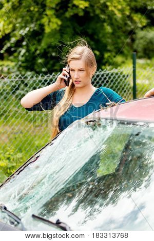 Woman dialing her phone after car crash