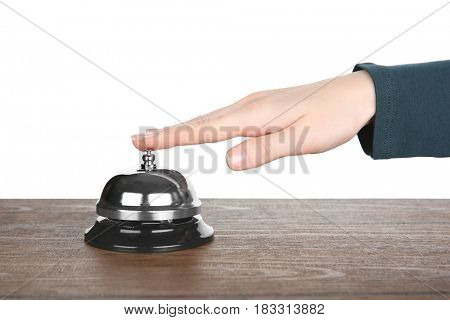 Female hand ringing a service bell on wooden table against white background