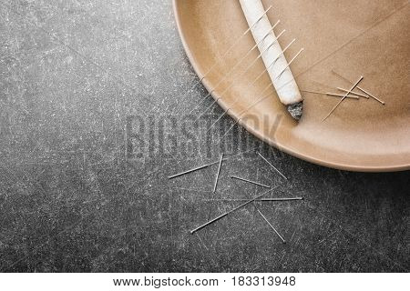 Plate with moxa stick and needles for acupuncture on dark textured background