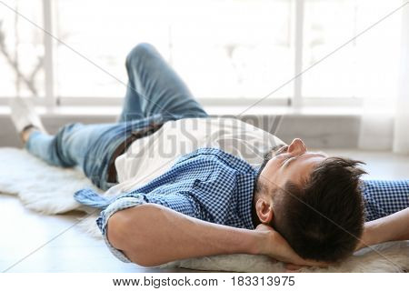 Happy young man lying on floor and taking rest