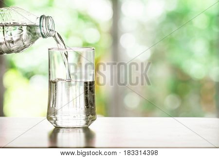 Close up pouring purified fresh drink water from the bottle on table in living room