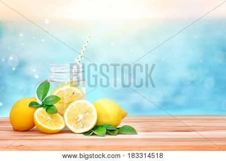 Citrus lemonade water with lemon sliced healthy and detox water drink in summer on wooden table with blue sea blur background