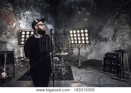 A bearded guy with musical instruments. Bearded guy with a microphone in the studio. Musician in a cap on the background of musical instruments