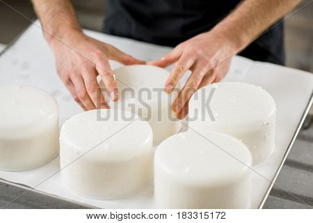Close-up of a man forming cheese into the plastic molds at the small producing farm