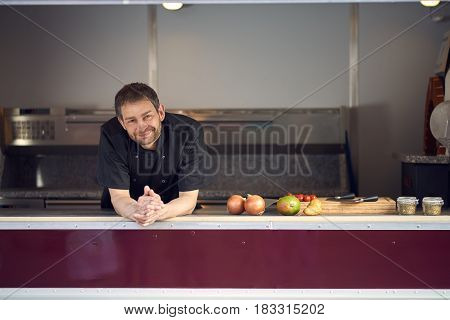 Smiling male chef in kitchen leaning on counter with cooking ingredients