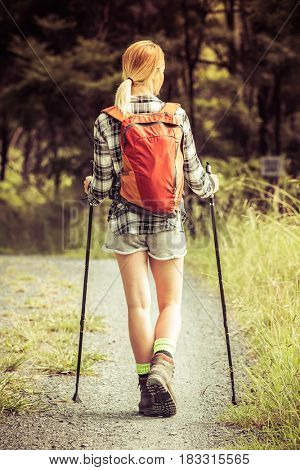 Young blond woman hiking on path