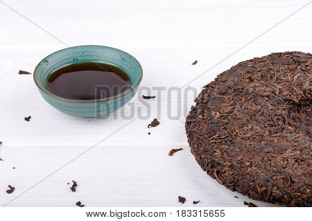 Round flat disc of puer tea and cup on white. Pressed Chinese fermented Pu-erh tea.