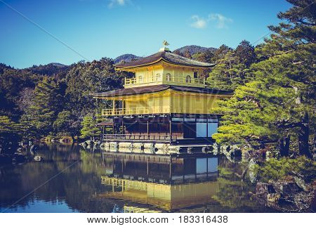 Beautiful Architecture of Kinkakuji Temple (The Golden Pavilion) reflected on surface of water. Tourism of Japan Kyoto during autumn season. Outdoor with blue sky and green trees. Vacation background