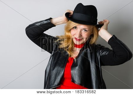 Beautiful woman with a black hat on a gray. Woman is forty years old.