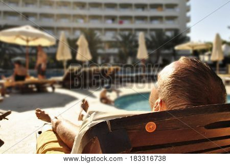 A man is sunning on a sun lounger at a hotel on vacation in Turkey